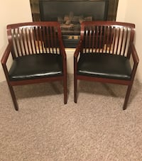 Two brown wooden framed black vinyl padded chairs