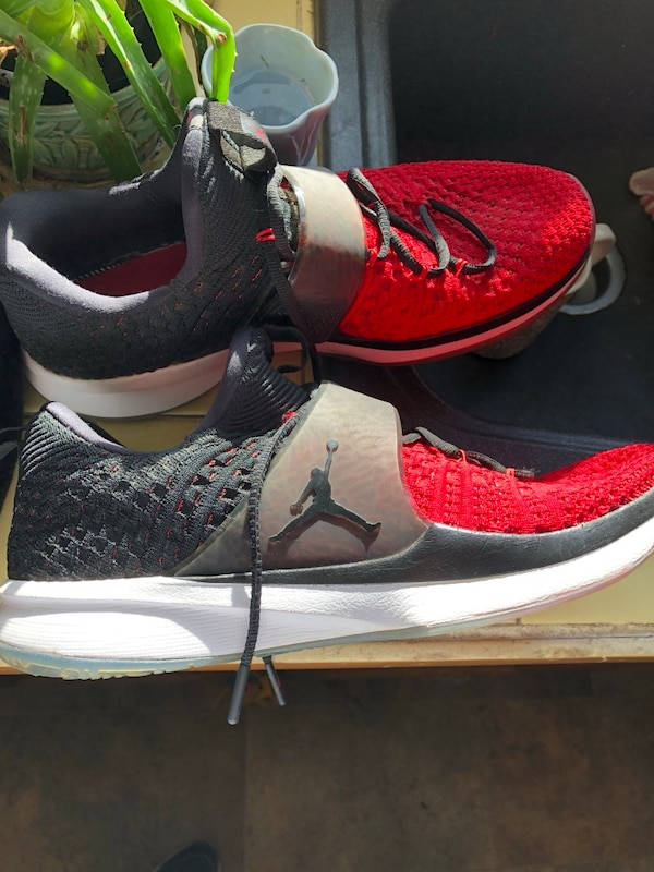 pair of gray-and-red Nike basketball shoes
