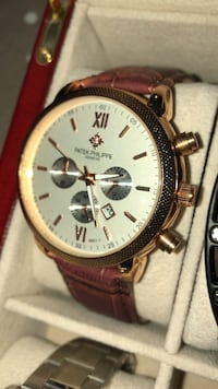 round gold chronograph watch with brown leather strap