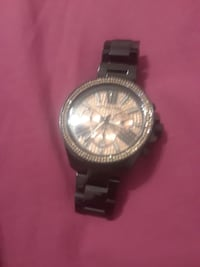 round silver chronograph watch with black strap