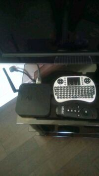 black MiniX TV box with remote control and flat screen TV