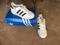 Brand new black and white tennis shoes that are brand name Adidas