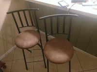 two brown padded black metal chairs