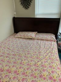 brown wooden bed frame with white and pink floral bedspread