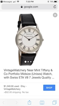 Round silver analog watch with black leather strap screenshot