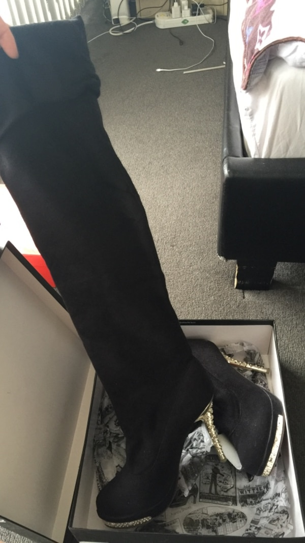 Pair of black pump-heeled tight-high boots