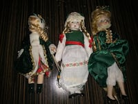 three assorted porcelain dolls with green dresses