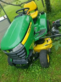 green and yellow John Deere ride-on lawn mower 145 mi