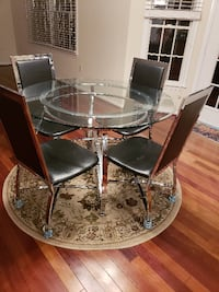 round clear glass top table with four chairs Fairfax
