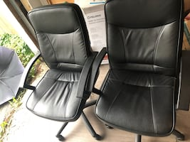 two black leather office rolling armchairs
