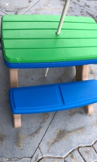 Kids bench with umbrella converts to water table.