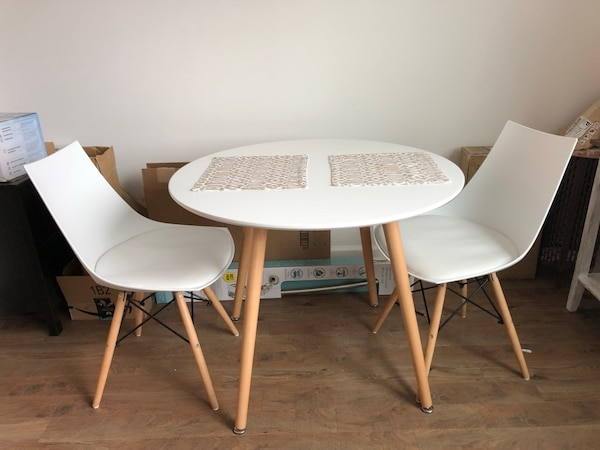 Round white wooden table with two chairs