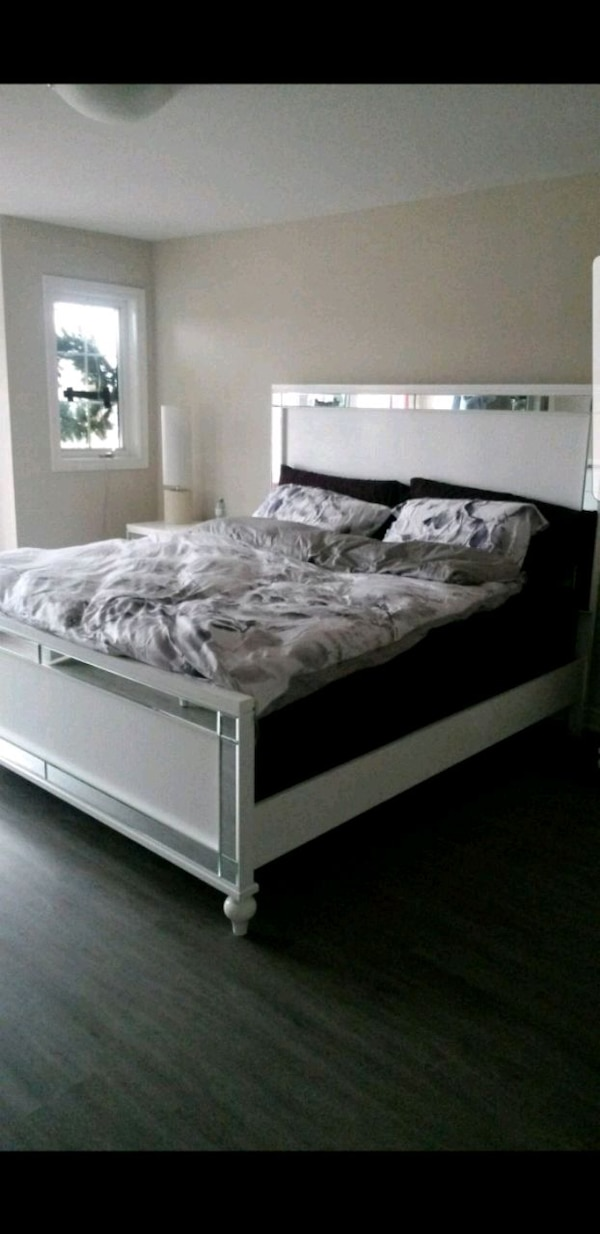 white wooden bed frame with white bed comforter