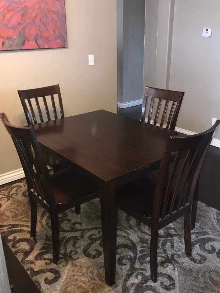 Rectangular dark-brown wooden table with four wooden chairs