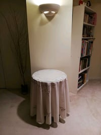 Round plywood table with table cloth and glass top