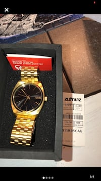 Gold nixon watch black face adjustable