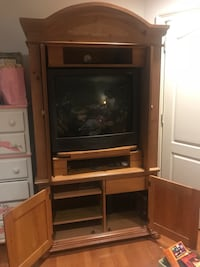 Black tv with brown wooden tv hutch  Hoover, 35244