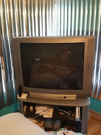 gray CRT television with brown wooden TV stand