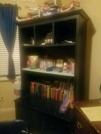 black wooden shelf and assorted-title book lot Mountain House