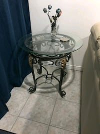 round clear glass top table with black metal base Markham