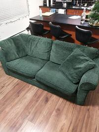 green fabric sofa with pull out bed.