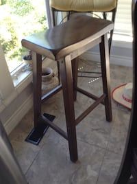 Brown wooden chair with black leather pad.  Real wood stool