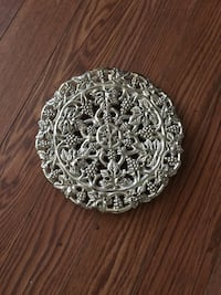 9 in silver plated trivet with legs, grapevine design. PU in Simp Simpsonville