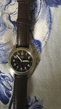 Round black swiss army analog watch with brown leather strap