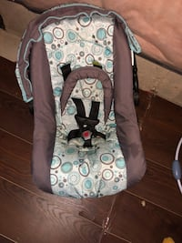 baby's brown, white, and teal car seat carrier