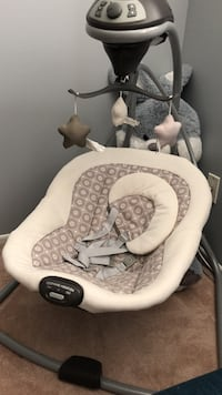 white and gray cradle and swing