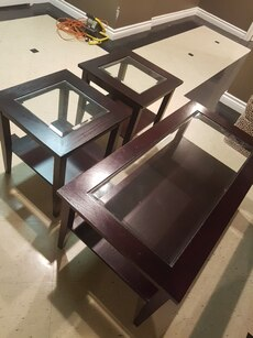 rectangular brown wooden framed glass top coffee table and two end tables