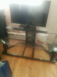 black flat screen TV; brown wooden TV stand Montréal, H1T 1J4