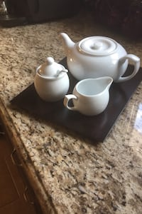 Teapot with sugar bowl and milk on a wood tray