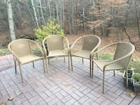 four gray wicker armchairs