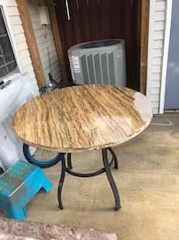 round brown wooden table with black steel base