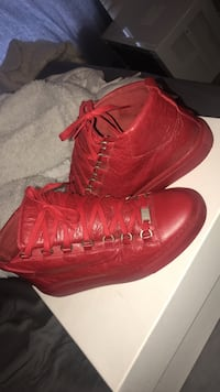 pair of red leather high-top sneakers