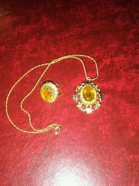 gold-colored pendant with rope-chain necklace