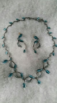 silver-colored and teal gemstone necklace matching with earrings