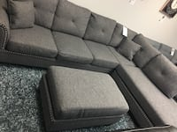 Fabric sectional with nailheads. Ash black color. Brand new. Ottoman $150 extra. 1154 mi