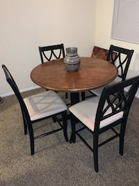 Round brown wooden table with four chairs dining set Pikesville