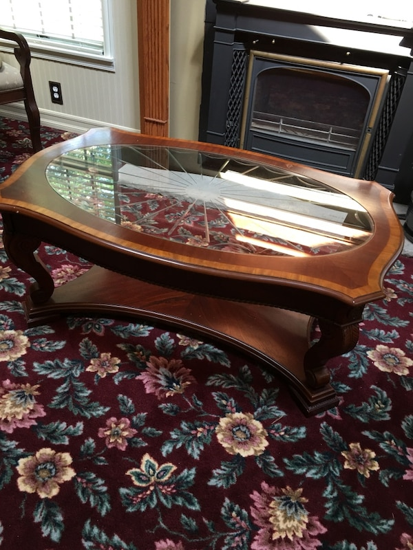 Brown ornate wooden framed glass top coffee table
