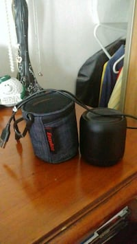 round black portable speaker with blue pouch