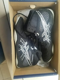 pair of black-and-white ASICS Showdown athletic shoes with box