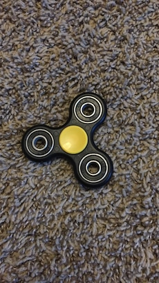 black and yellow tri-spinner fidget toy