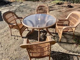 Round brown Wicker table with four wicker chairs with/ umbrella hole.