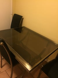 Rectangular glass top dining table with gray steel base