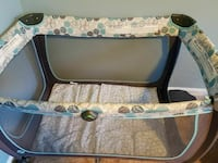 white and brown travel cot