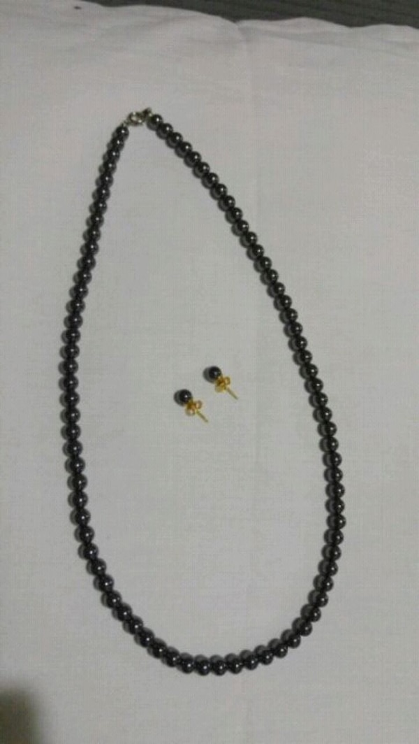 black pearl necklace and pair of earrings