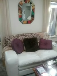 white leather 2-seat sofa and three pillows