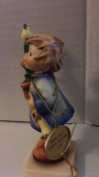 Brown haired toddler in blue dress ceramic figurine
